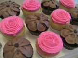 Pink ribbon roses atop very vanilla cupcakes alongside chocolate petal flowers on chocolate paradise cupcakes. An enticing assortment.