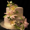Beautiful edible flowers adorn this very vanilla cake with vanilla buttercream icing, finished off with mauve fondant covering.