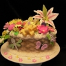 Pretty garden basket. This cake highlights basketweave design, fondant bow and bugs and fondant/gumpaste flowers. Almost any flower is possible to be made sweetly edible.